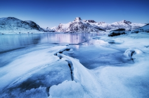 Norway - Mountain ridge and ice on the frozen lake surface